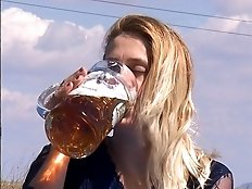 Lovely lady with golden hairs is drinking golden urine from can
